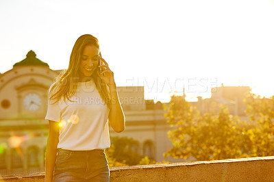 Buy stock photo Shot of a woman talking on her cellphone while standing on a rooftop