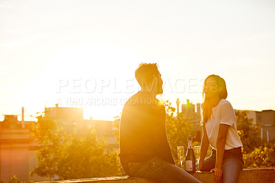 Buy stock photo Shot of a couple having drinks while on a rooftop date