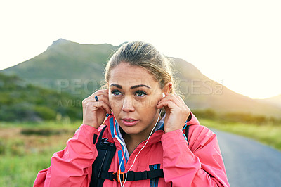 Buy stock photo Cropped shot of an attractive young female athlete listening to music while out for a morning run