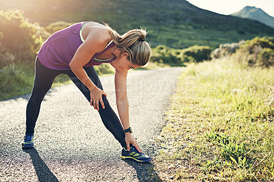 Buy stock photo Full length shot of an attractive young female athlete stretching before her morning run