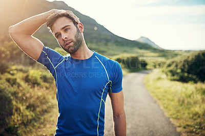 Buy stock photo Cropped shot of a handsome young male athlete stretching before his run outdoors