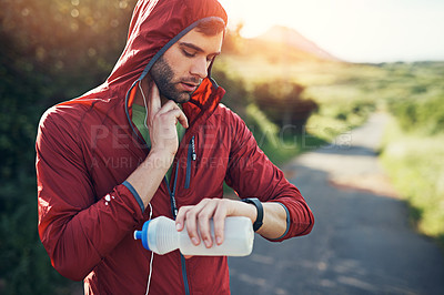 Buy stock photo Cropped shot of a handsome young male athlete tracking his pulse while out for a morning run