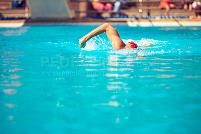 Buy stock photo Shot of an unrecognizable young male swimmer doing freestyle in a swimming pool