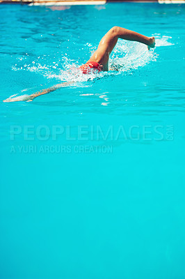 Buy stock photo High angle shot of an unrecognizable young male swimmer doing freestyle in a swimming pool