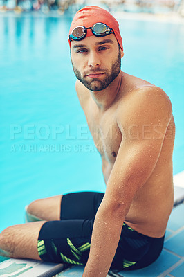 Buy stock photo Cropped portrait of a handsome young male swimmer sitting on the side of a pool