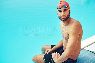 Buy stock photo High angle portrait of a handsome young male swimmer sitting on the side of a pool