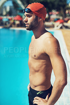 Buy stock photo Cropped shot of a handsome young male swimmer standing with his hands on his hips by the pool