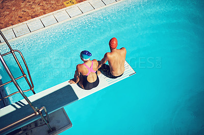 Buy stock photo High angle shot of two young swimmers sitting on a diving board