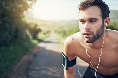 Buy stock photo Cropped shot of a handsome young male athlete looking tired during his morning run