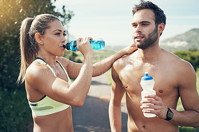Buy stock photo Cropped shot of an affectionate young couple taking fluids on board while out for their morning run