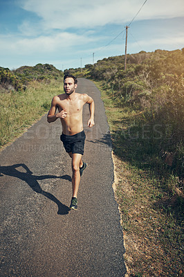 Buy stock photo High angle shot of a handsome young male athlete out for a morning run