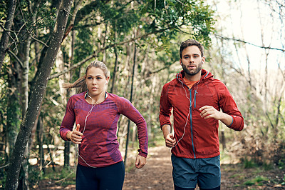 Buy stock photo Cropped shot of a young athletic couple listening to music while out for their morning run