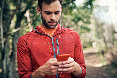 Buy stock photo Cropped shot of a handsome young male athlete checking his messages while out for a morning run