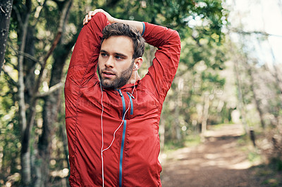 Buy stock photo Cropped shot of a handsome young male athlete stretching before beginning his morning run