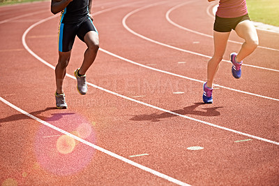 Buy stock photo Shot of two unrecognizable athletes racing on the track