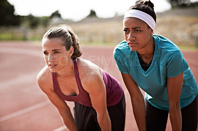 Buy stock photo Cropped shot of two young athletes out on the track