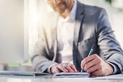 Buy stock photo Closeup shot of an unrecognizable businessman writing notes while working on a computer in an office