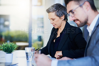 Buy stock photo Shot of two businesspeople working in an office