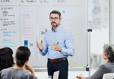 Buy stock photo Shot of a mature businessman giving a presentation in an office