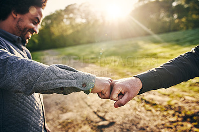 Buy stock photo Cropped shot of two men fist bumping while team building at a company retreat