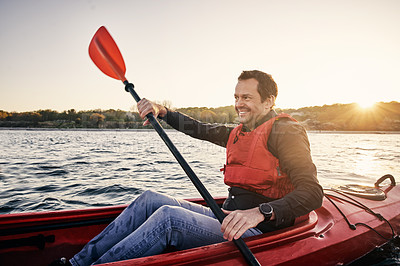 Buy stock photo Cropped shot of a handsome man canoeing all by himself on a lake in the forest