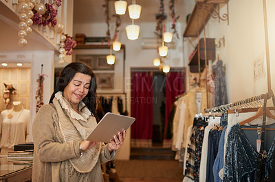 Buy stock photo Cropped shot of an attractive mature female entrepreneur working on a tablet in her self-owned boutique