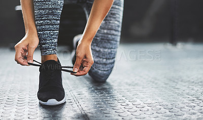 Buy stock photo Cropped shot of a woman tying her shoelaces in a gym