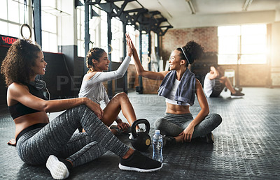 Buy stock photo Shot of young women giving each other a high five while taking a break at the gym