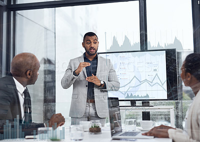 Buy stock photo Shot of a young businessman delivering a presentation to his colleagues in the boardroom with cgi graphs superimposed against them