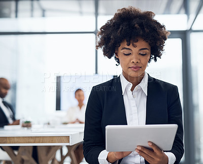 Buy stock photo Shot of a young businesswoman using a digital tablet in a boardroom with her colleagues in the background
