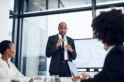 Buy stock photo Shot of a mature businessman delivering a presentation to his colleagues in the boardroom of a modern office