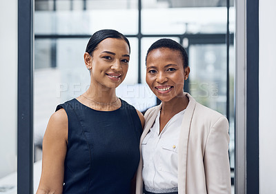 Buy stock photo Portrait of two confident businesswomen working together in a modern office