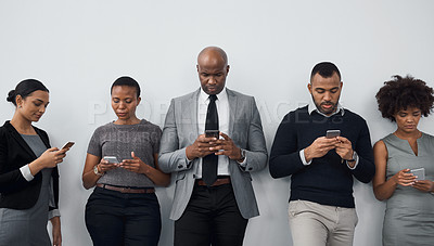 Buy stock photo Studio shot of a group of businesspeople using wireless technology while waiting in line against a gray background