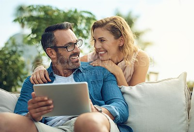 Buy stock photo Cropped shot of an attractive mature woman checking in with her husband while he browses the web using a tablet outdoors