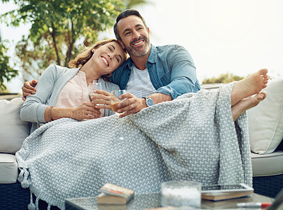 Buy stock photo Full length shot of an affectionate mature couple drinking wine while relaxing on a sofa outdoors