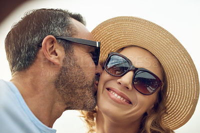 Buy stock photo Cropped shot of a handsome mature man taking a selfie while kissing his wife on the cheek