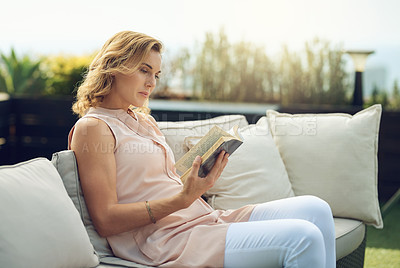 Buy stock photo Cropped shot of an attractive mature woman reading a book while sitting outside