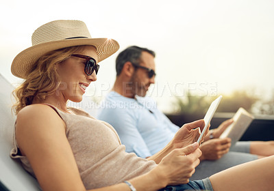 Buy stock photo Cropped shot of an attractive mature woman using a tablet while relaxing outdoors with her husband