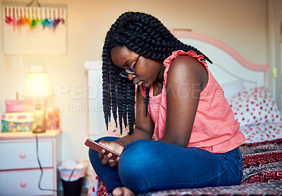 Buy stock photo Cropped shot of an adorable little girl sitting on her bed using a cellphone in her bedroom