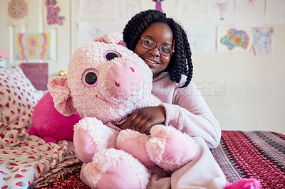 Buy stock photo Portrait of an adorable little girl holding a plush toy while sitting on her bed in her bedroom