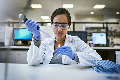 Buy stock photo Shot of a young woman transferring liquid from a pipette to a test tube in a laboratory