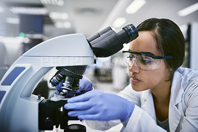 Buy stock photo Shot of a young woman using a microscope while working in a laboratory