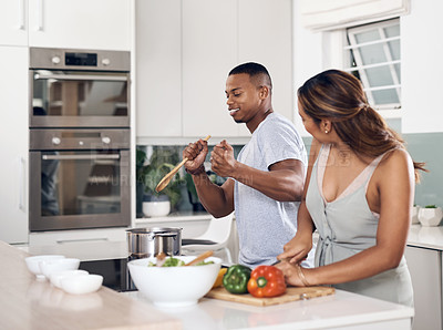 Buy stock photo Shot of a young couple singing while cooking together at home