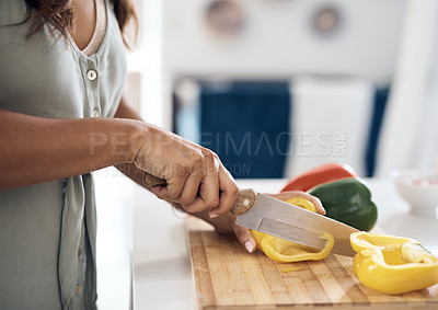 Buy stock photo Closeup shot of an unrecognizable woman cutting peppers at home