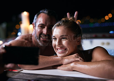 Buy stock photo Cropped shot of an affectionate mature couple taking selfies on their cellphone while relaxing in a hot tub