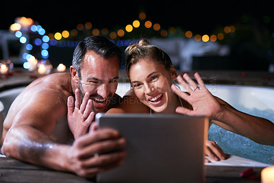 Buy stock photo Cropped shot of an affectionate mature couple video chatting on their tablet while relaxing in a hot tub