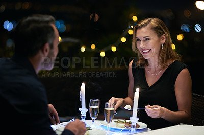 Buy stock photo Cropped shot of an attractive mature woman sitting at a dinner table while on a date with her husband