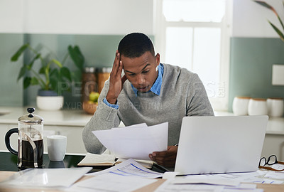 Buy stock photo Shot of a young man looking stressed out while going through paperwork at home