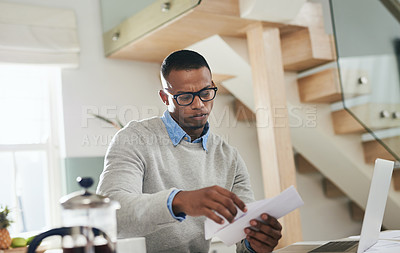 Buy stock photo Shot of a young man going through paperwork at home