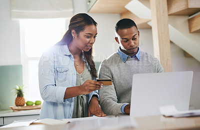 Buy stock photo Shot of a young couple using a credit card and laptop together at home